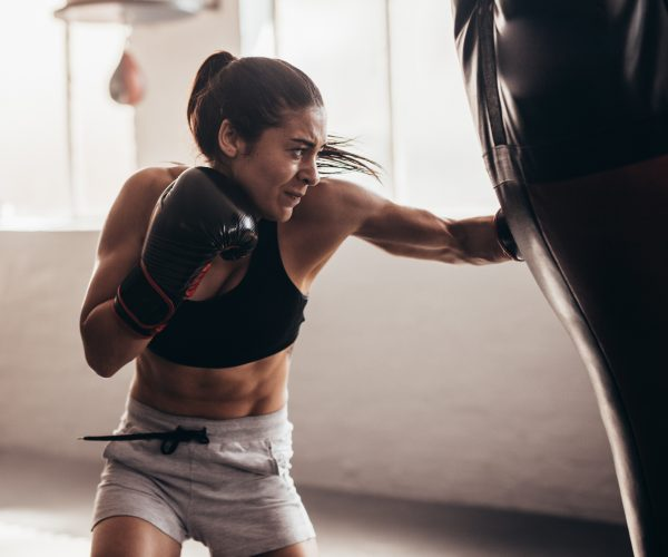 Female boxer hitting a huge punching bag at a boxing studio. Woman boxer training hard.