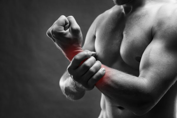 Pain in the hand. Muscular male body. Handsome bodybuilder posing on gray background. Black and white photo with red dot