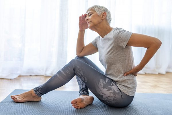 Mature Woman suffering from lower back pain. Mature woman resting with back pain. Female lower back pain. Senior woman injury suffering from backache cause of fitness.
