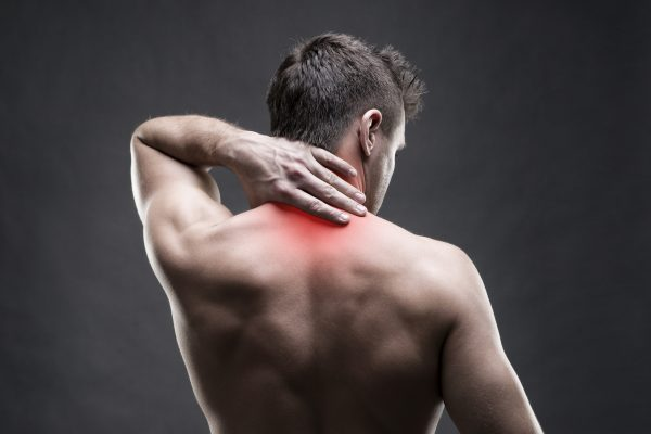 Pain in the neck. Man with backache. Muscular male body. Handsome bodybuilder posing on gray background with red dot