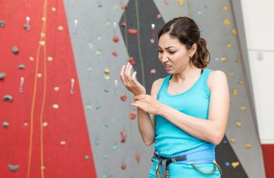woman climber with the trauma and pain in the wrist on a background of climbing wall